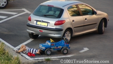 Kids imitating adults: A little boy under his toy car